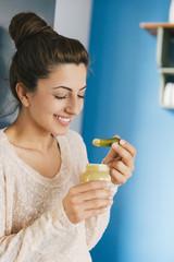 Junge schwangere Frau isst Essiggurke mit Senf in ihrer Küche