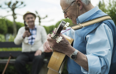 Zwei alte Männer mit Gitarre im Park