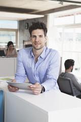 Mann mit Tablet-Computer im Büro