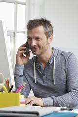 Mann am Schreibtisch mit Handy