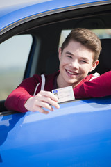 Teenager sitzt im Auto und zeigt Führerschein