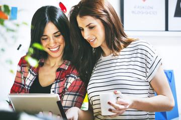 Zwei weibliche Mode-Blogger mit Tablet-PC