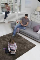 Mutter, Vater und Tochter mit tragbaren Geräten im Wohnzimmer