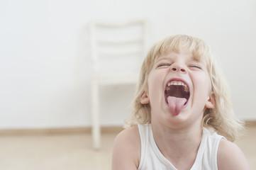 Portrait des kleinen Jungen mit ausgestreckten Zunge