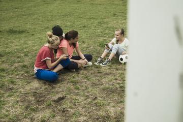 Vier Teenies auf Fußballplatz mit ihren Smartphones
