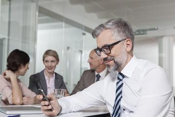 Geschäftsleute im Konferenzraum, Mann kriegt eine SMS