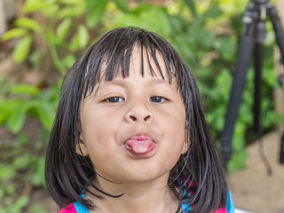 Little asian girl sticking the tongue out
