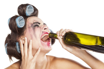 Crying drunk young woman with curlers drinking wine from bottle