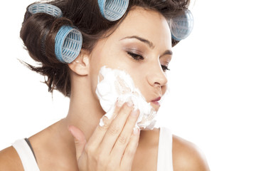 attractive young woman applying shaving foam on her face