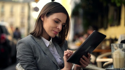 Pretty young businesswoman using tablet computer, sitting in caf