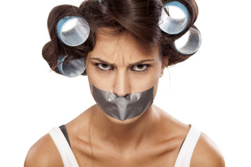 angry housewife with curlers and adhesive tape over her mouth