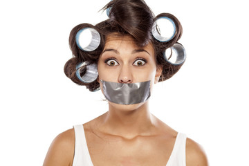 shocked housewife with curlers and adhesive tape over her mouth