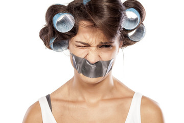 angry woman with curlers and adhesive tape over her mouth