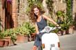 Young beautiful italian woman sitting on a italian scooter.