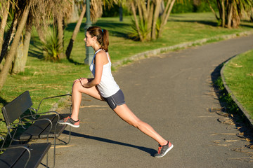 Female athlete warming up and stretching for running