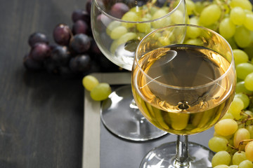 glass of white wine and assorted grapes on a blackboard