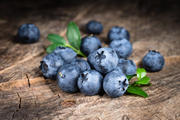 Blueberry with leaves on wooden background