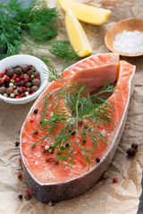 raw salmon steak, lemon, spices prepared for cooking, vertical