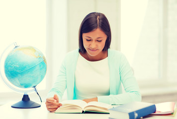 teacher with globe and book at school