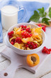 Cornflakes in bowl with red сcurrant
