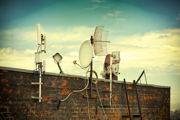 satellite dishes on the roof. Photo toned in yellow