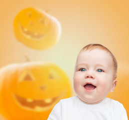 smiling baby over pumpkins background