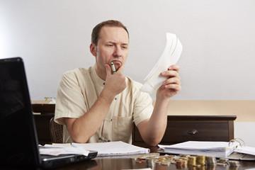 Mann bei der Buchführung, am grübeln
