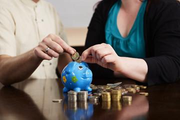 Sparen, Geldmünzen in den Sparschwein werfen