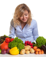 Frau mit blonden Locken prüft das Gemüse