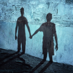 Silhouette of two people holding hands