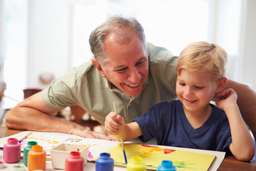Grandfather Painting Picture With Grandson At Home