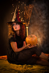 Woman dressed like a witch and holding a pumpkin