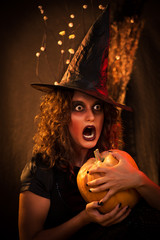 Woman with scared face dressed like a witch and holding pumpkin