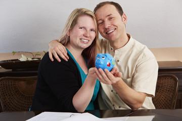 Sparen, Ehepaar hält Sparschwein in den Händen