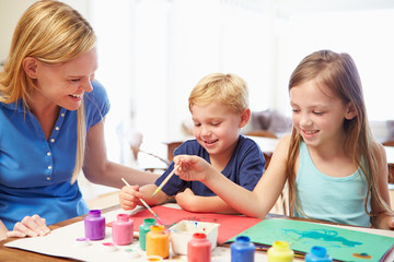 Mother Painting Picture With Children At Home
