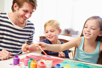 Father Painting Picture With Children At Home