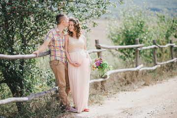 Pregnant woman with her husband on the mountains background