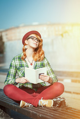 Hipster woman in hat and glasses with book
