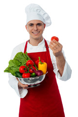 Male chef holding a fresh vegetables