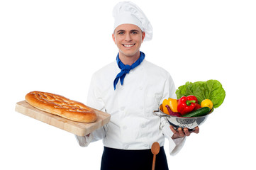 Smiling chef holding bread and vegatables