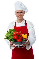 Smiling male chef with fresh vegetables