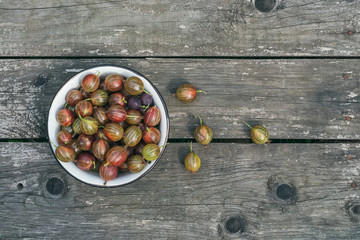 A bawl of gooseberries on a wooden surface