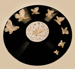 Old vinyl record with paper butterflies, close up