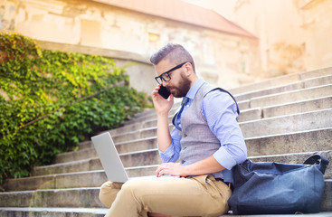 Hipster businessman with phone and laptop