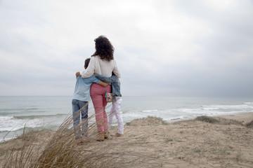 Madre e hijos abrazados mirando el mar