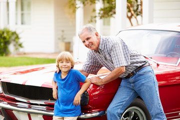 Portrait Of Grandfather And Grandson With Restored Car