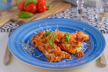 cannelloni pasta dish with tomatoe sauce on a blue plate with to