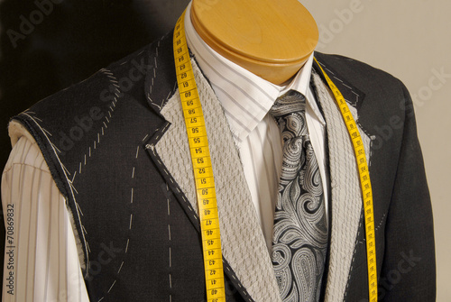 Tailor shop mannequin with measuring tape across neck. - 70869832
