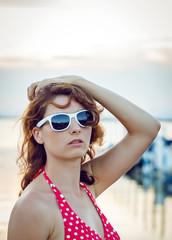 Young woman in red bikini on harbour.