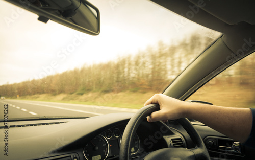 Male driver hands on steering wheel of a car and road - 70870262